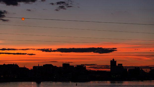 Kaupungin silhuetti piirtyy laskevan auringon säteitä vasten.