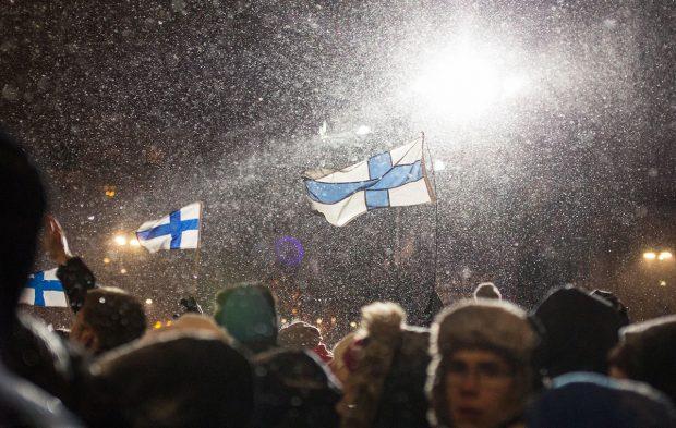 Kisayleisöä Salpausselällä. Illan ilotulitus menossa. Suomen liput liehuvat.