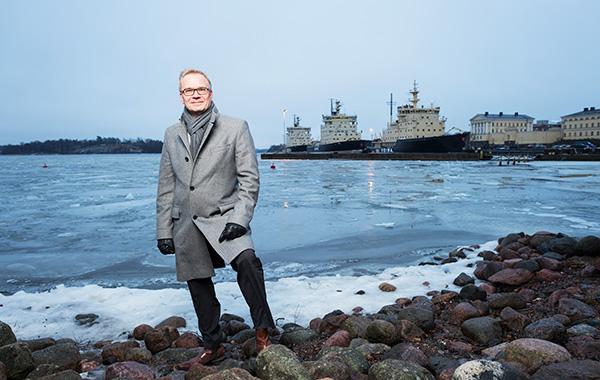 Timo Lehtimäki seisoo meren rannalla. Taustalla näkyy Katajannokka ja laiturissa olevia jäänmurtajia.