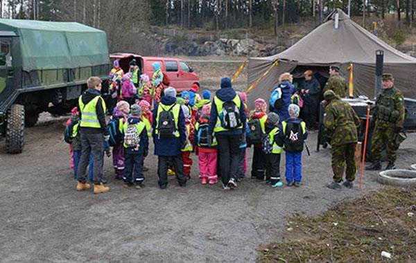 Päiväkotiryhmän lapset tutustuvat Puolustusvoimiin. Kohteina soppatykki, joukkueteltta ja kuorma-auto. Sotilaat opastavat lapsia.