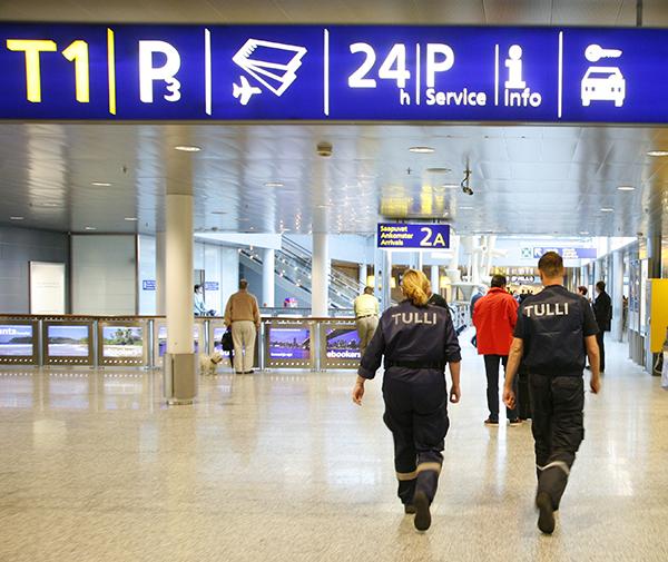 Kaksi Tullin työntekijää astelee Helsinki-Vantaan lentoaseman käytävällä.