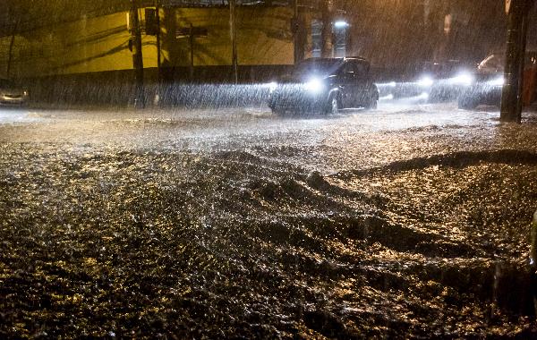 Myrsky on aiheuttanut tulvan kaduille. Auto tulvivalla kadulla.