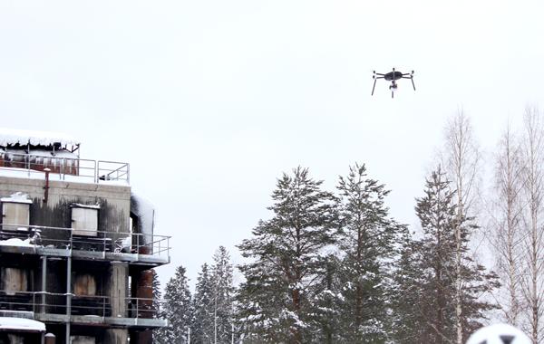 Drone lentää palaneen kerrostalon läheisyydessä.