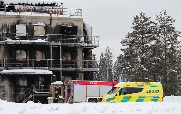 Palanut kerrostalo, jonka edessä paloauto ja ambulanssi.