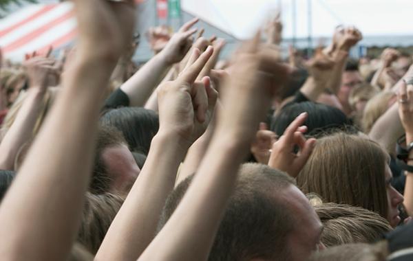 Yleisötapahtumassa tiivis väkijoukko kädet pystyssä.