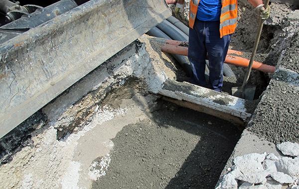 Katu kaivettu auki, kaivannon poikki kulkee kaapeli.