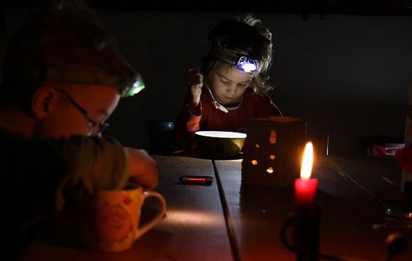 Pimeässä sähkökatkon aikaan. Kynttilä ja otsalamput antavat valoa.