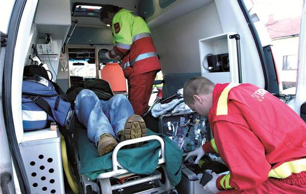 Ensihoitajat hoivaavat paareilla makaavaa potilasta ambulanssissa.