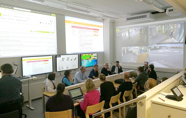 Johtokeskuksen henkilötöä yhteisen työpöydän ääressä. Tilan seinällä näkyvät isot tilannekuvanäytöt.
