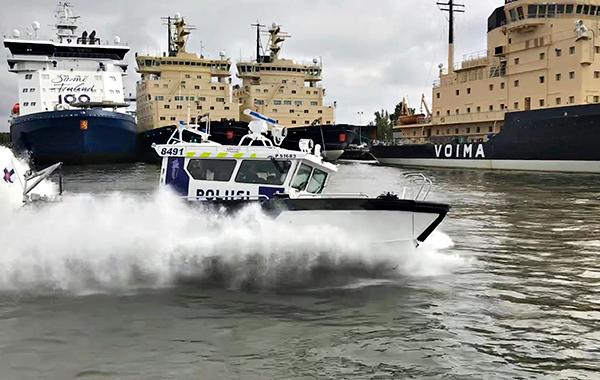 Poliisivene vauhdissa, taustalla näkyvät laiturissa olevat jäänmurtajat.