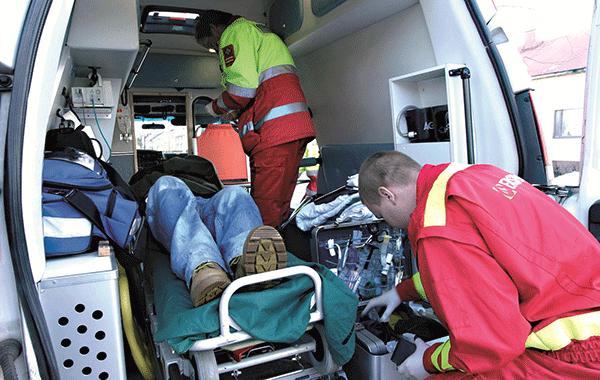 Kaksi ensihoitajaa hoivaa potilasta ambulanssissa.