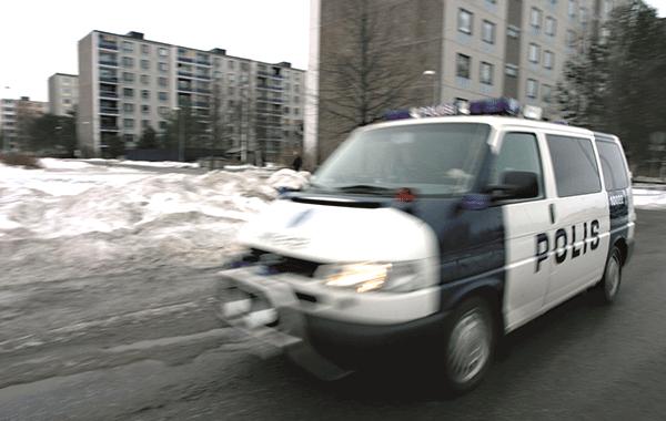 Poliisiauto ajaa loskaisessa talvimaisemassa lähiön kaduilla.