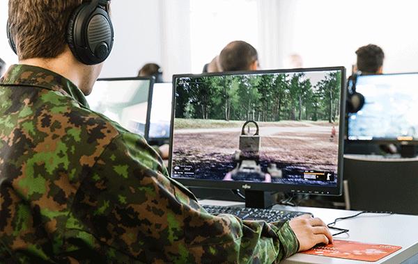 Sotilas tarkkailee näyttöpäätteeltä kuvaa maastosta.