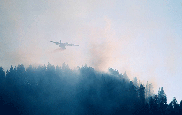 Lentosammutusta, lentokone lentää metsäpaloalueen yllä.