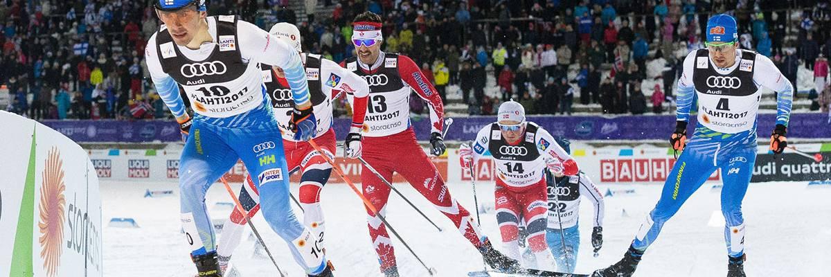 Miesten sprintin hiihtäjät vauhdissa.