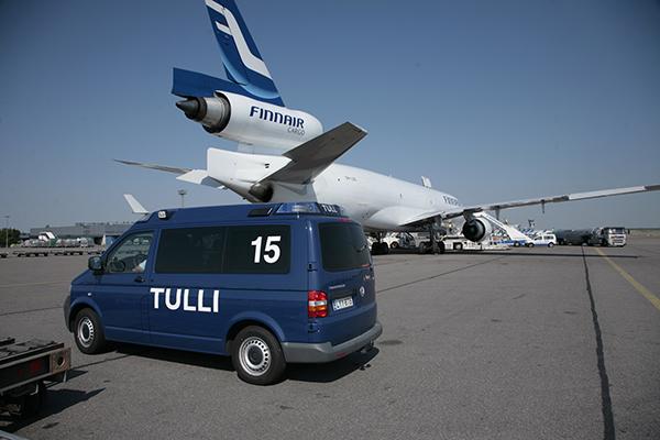 Tullin pakettiauto lentokentällä. Taustalla näkyy matkustajalentokone.