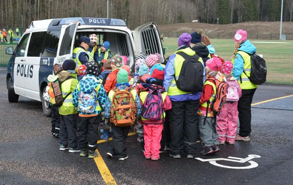 Päiväkotiryhmän lapset ovat päässeet tutustumaan poliisiautoon. Kiinnostus on suurta.