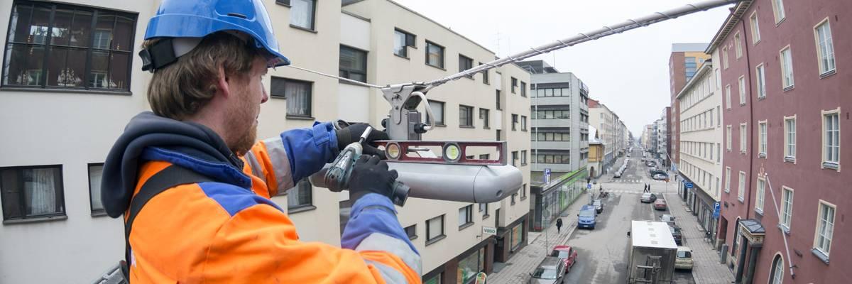 Sähköasentaja asentaa led-katuvaloja korkealla katutason yläpuolella.