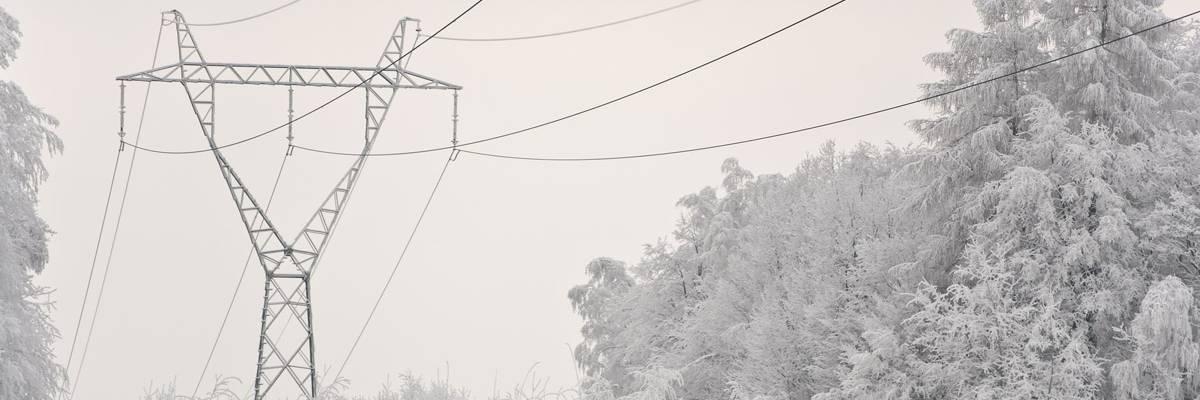 Sähköverkon korkeajännitelinjaa utuisessa pakkasmaisemassa.
