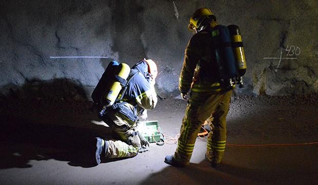 Pelastushenkilöstöä pimeässä metrotunnelissa.