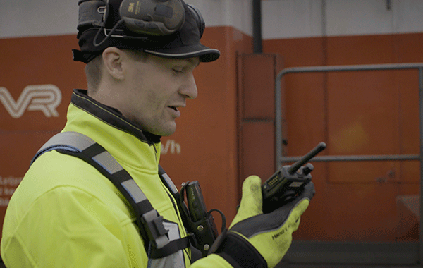 Rautateiden työntekijä Virve-puhelin kädessään. Taustalla veturi.
