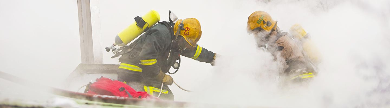 Kaksi savusukeltajaa työssään sankan savun keskellä.