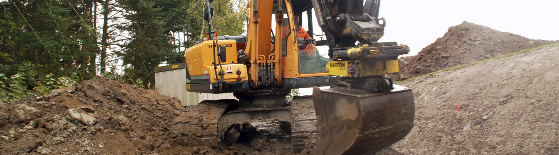 Kaivinkone kaapelia kaivamassa.