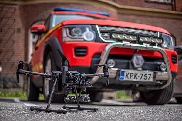 Drone maassa paloauton edessä.
