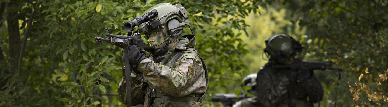 Sotilas taisteluvarusteissa tähtää rynnäkkökiväärillä.