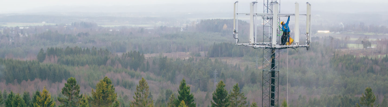 Ilmakuva, jossa asentaja työskentelee linkkimaston huipulla. Taustalla näkyy avaraa metsämaisemaa.