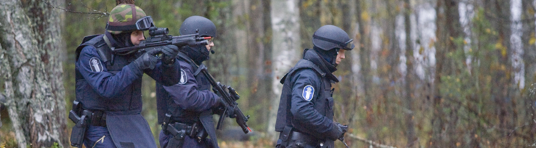 Kolme aseistettua poliisia metsässä.