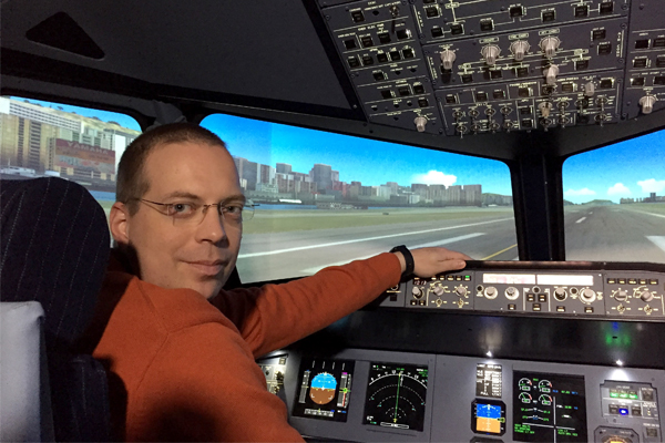 Mies istuu lentosimulaattorin ohjaamossa.