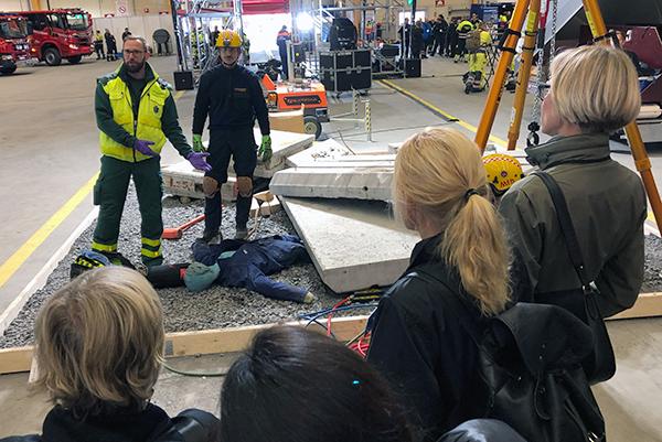 Pelastusharjoituksen opetustilanne, jossa esitellään toimia kaatuneen betonielementin alle jääneen uhrin pelastamiseksi.