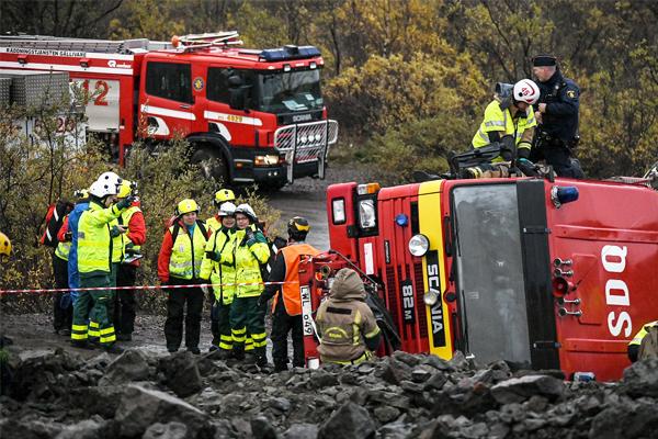 Paloauto kaatunut kyljelleen. Pelastushenkilöstöä korjaamassa tilannetta.