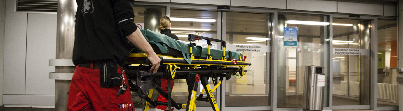 Ensihoitajat työntävät paareja kohti Meilahden sairaalan ulko-ovea.