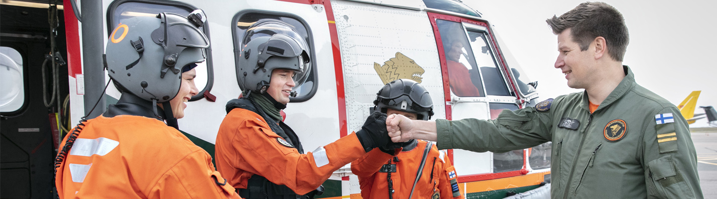 Rescue personnel greet each other in front of a helicopter.