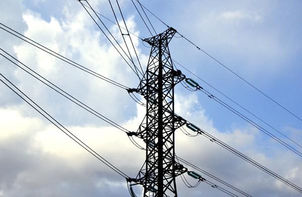 Korkeajännitelinja. Sähköpylväs ja johdot näkyvät taivasta vasten.