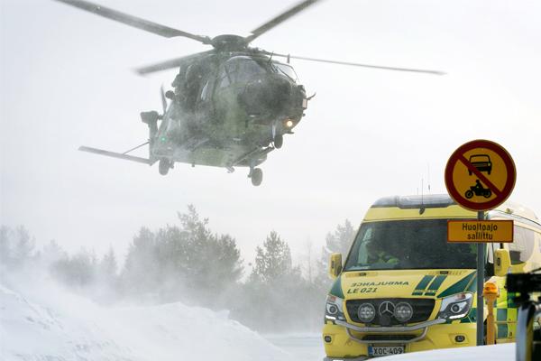 Talvisella tiellä ensihoitoyksikön ambulanssi ja puolustusvoimien helikopteri.