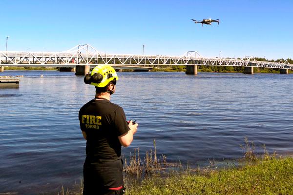 Ylipalomies Risto Tolonen Lapin Pelastuslaitokselta lennättää dronea tulva-alueen yläpuolella.
