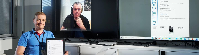 Tuotantopäällikkö Esa Wörlin työpöytänsä äärellä, taustalla ruudulla näkyy etäyhteydessä oleva turvallisuuspäällikkö Mikko Kosonen.