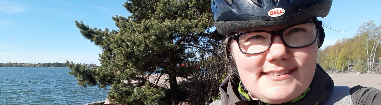 Krivatin tuoteomistaja Elina Koski pyöräilemässä meren rannalla.
