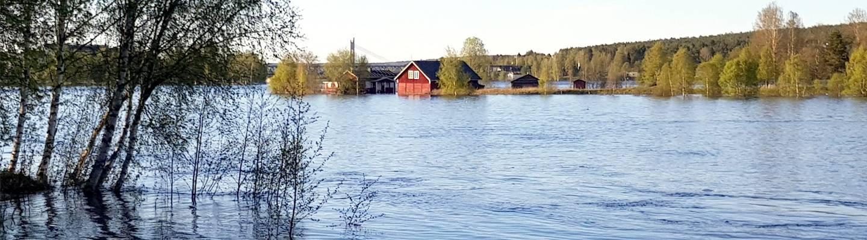 Tulviva joki. Veden saartamia rakennuksia.