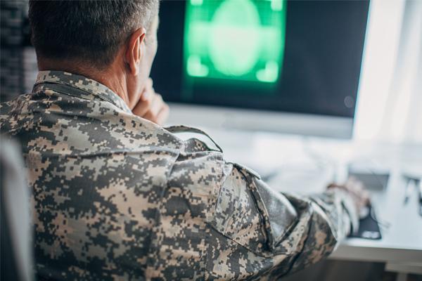 Sotilasasuinen mies käyttää tietokonetta.