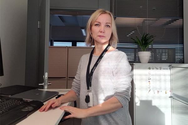 Erillisverkkojen ryhmäpäällikkö Katja Lamminen seisoo työpöytänsä ääressa.