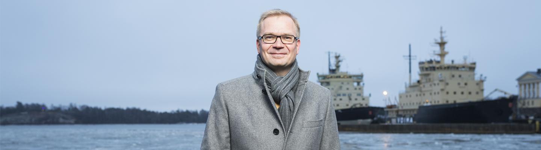 Erillisverkkojen toimitusjohtaja Timo Lehtimäki seisoo merenrannassa taustallaan laiturissa olevat jäänmurtajat.