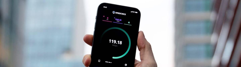 Käsi, jossa on matkapuhelin, jonka näytössä on 5G-nopeustesti