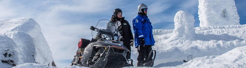 Poliisi, erävalvoja ja moottorikelkka lumisessa Lapissa