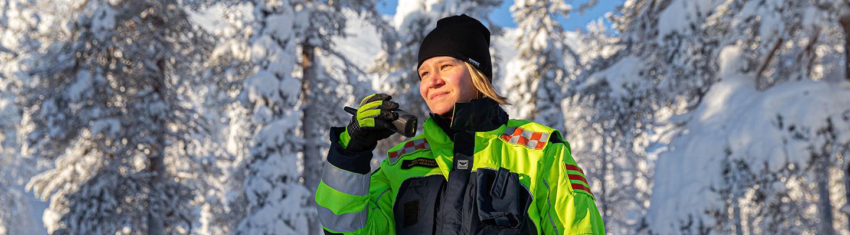Kirsti Heikkala pitelee Virve-puhelinta kädessään Lapin lumisessa maastossa.