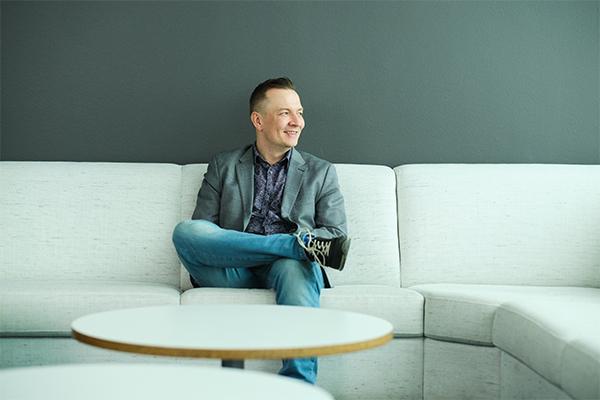 Antti Kauppinen istuu sohvalla ja hymyilee.
