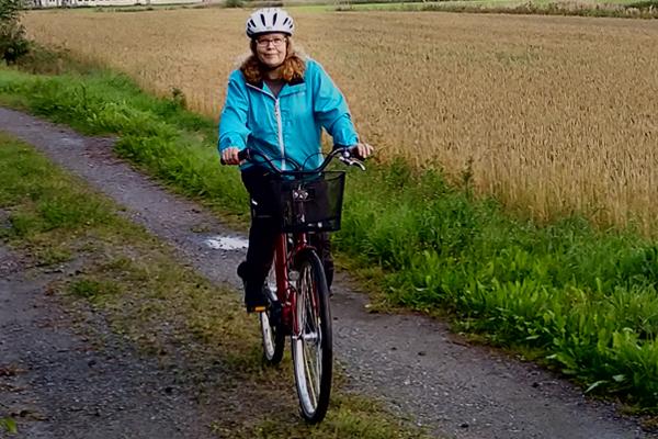 Tuija Kujanpää pyöräilemääs maalaismaisemassa.